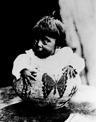 Baby sitting in a basket with a butterfly design woven onto the basket