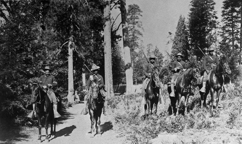 Five African-American mounted infantrymen on horseback in a forest