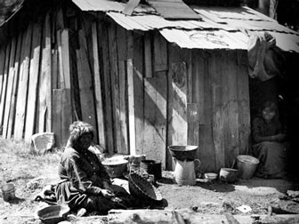 Callipene & Lena Brown sitting outside a cabin. Lena Brown sits by the doorway smiling as Callipene appears to be sitting among her baskets while taking a break from basket weaving.