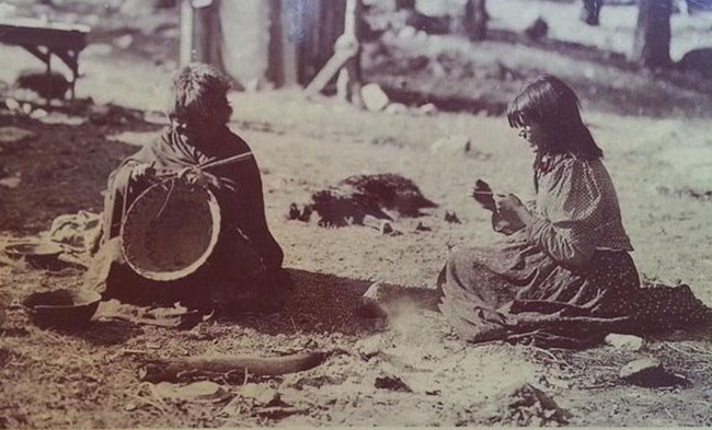 Two American Indian women weaving