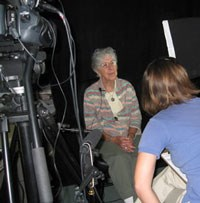 Woman sits in front of camera being interviewed