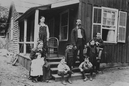 Family of 9 stands on their home's porch
