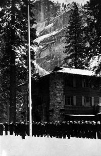 WWII soldiers stand outside the Ahwahnee in snow by a flagpole