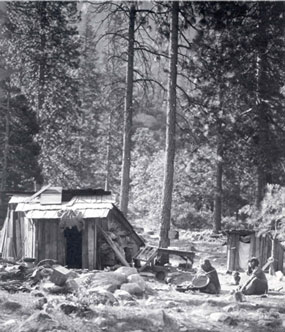 Two American Indians sit on ground by their simple housing