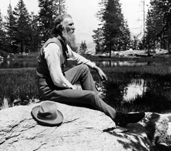 John Muir sits on rock with lake behind