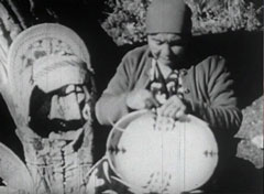 An American Indian woman makes baskets