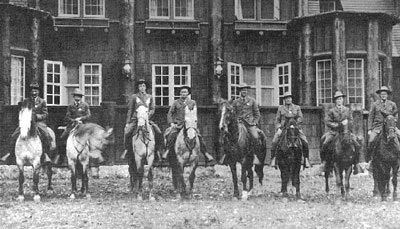 Eight mounted rangers pose in front of big windows on the Rangers' Club where they lived