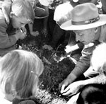 Ranger leans down to show children plant in historic photo