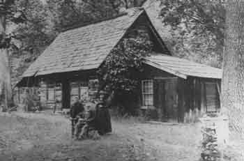 Family poses in front of historic cabin