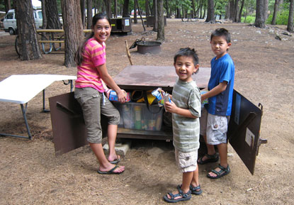 3 children stand next to an open bear box filled properly with their human food