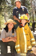 Child in a firefighter uniform poses with two rangers