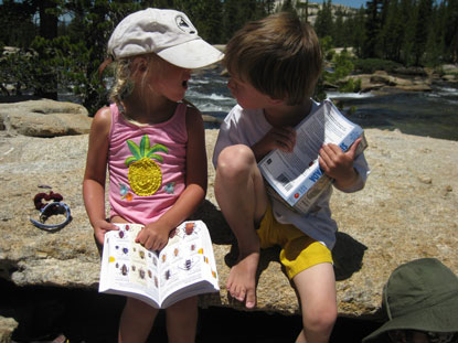 Two children converse with wildlife guide ID books in hand