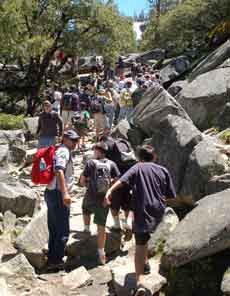 A large numbers of hikers walk up the rocky Mist Trail on a summer day.