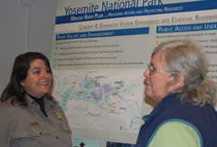 Ranger speaks with public meeting participant in front of park display board