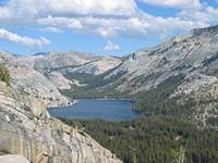 Image of Tenaya lake and surrounding granite cliffs and domes.
