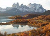 Ragged peaks rise behind a river with fall colors