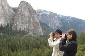 Two people hold binoculars to face while birding