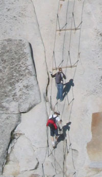 Two men hang onto cables ascending rockface