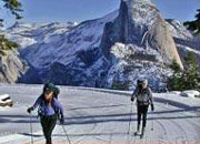 Two people cross-country ski with Half Dome in background