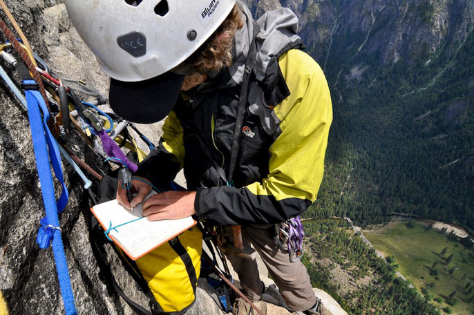 Rock climber on the side of El Capitan making notes in a notebook