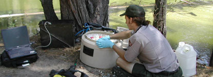 A hydrologist reaches into a water sampling machine