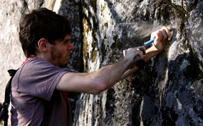 Scientist chisels rock to collect lichen sample