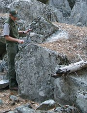 Ranger holds tool above rock fall rubble
