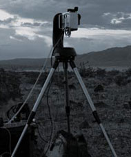 Camera on tall tripod is placed in open meadow to snap landscape images