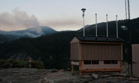 An air quality monitoring station sits on top of a mountain with a fire behind it