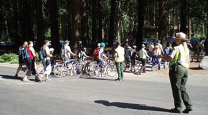 Ranger motions bikers to cross the street