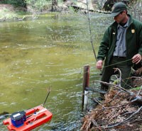 Ranger stands alongside river with water tester