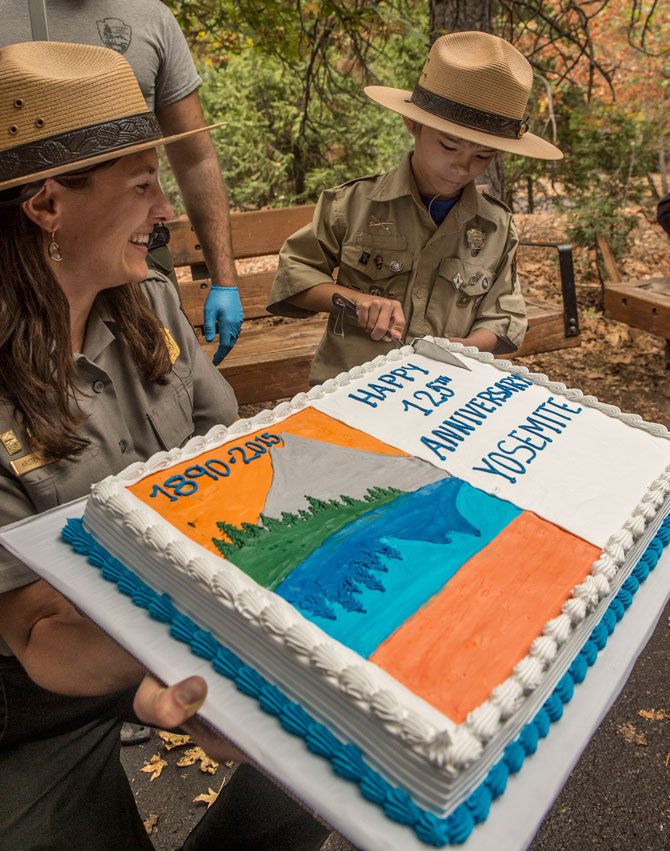 "Gabriel Lavan-Ying, better known as ""Ranger Gabriel,"" cuts a commemorative anniversary cake at the conclusion of Yosemite National Park's 125th Anniversary celebration."