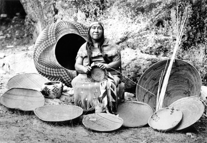 Indian woman surrounded by baskets