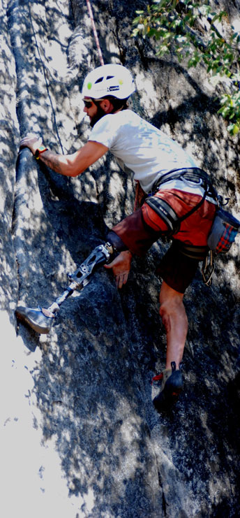 Rock climber with prosthetic leg climbing a cliff