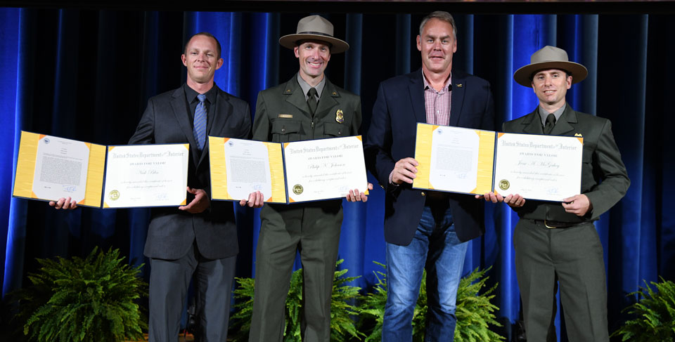 Three rangers and the Interior secretary on stage displaying award certificates