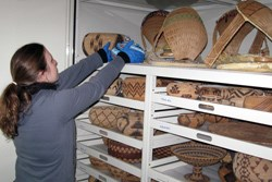 Museum employee working with historic baskets