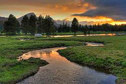 Sunset over a grassy meadow with a river running through it.