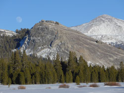 Granite dome overlooking a snowy meadow.