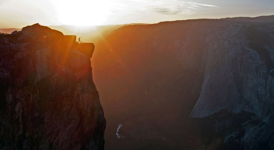 Person standing near the edge of a cliff, watching the sun set.
