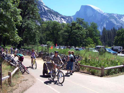 Bicyclists riding down bike path with Half Dome in background