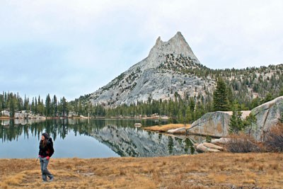 Hiker next to a lake with a mountain in the background