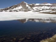 A cirque rises behind a partially snow covered Gaylor Lake