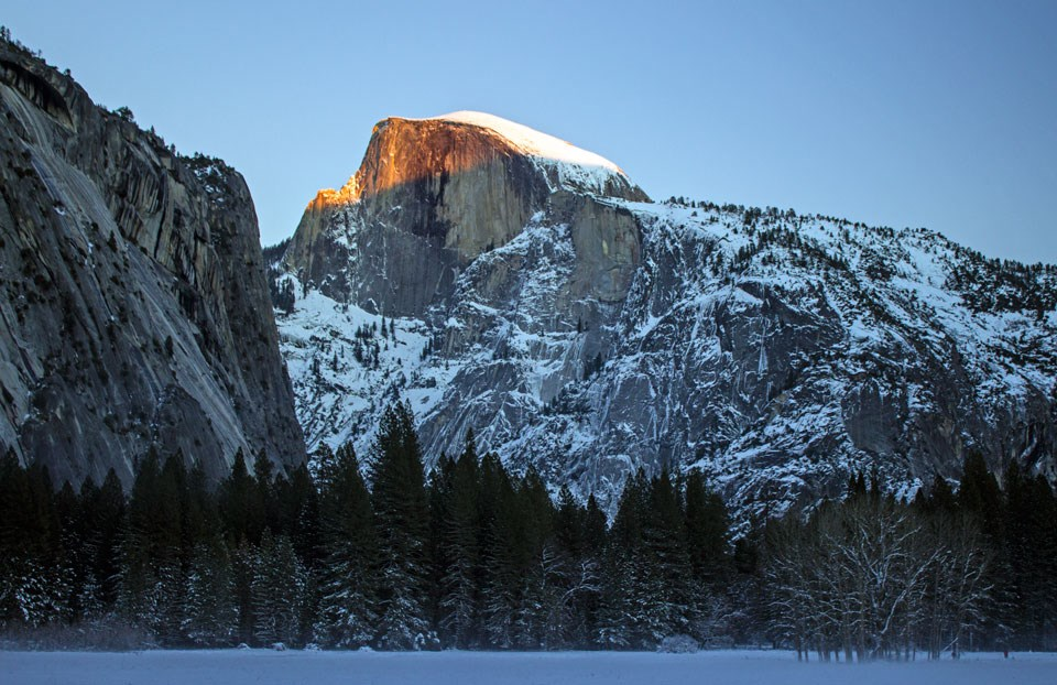 Orange light on the face of Half Dome with a snowy meadow in the foreground.