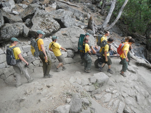 Rescuers wheel a litter with patient down the trail
