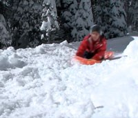 Child sledding down a snowy hill.