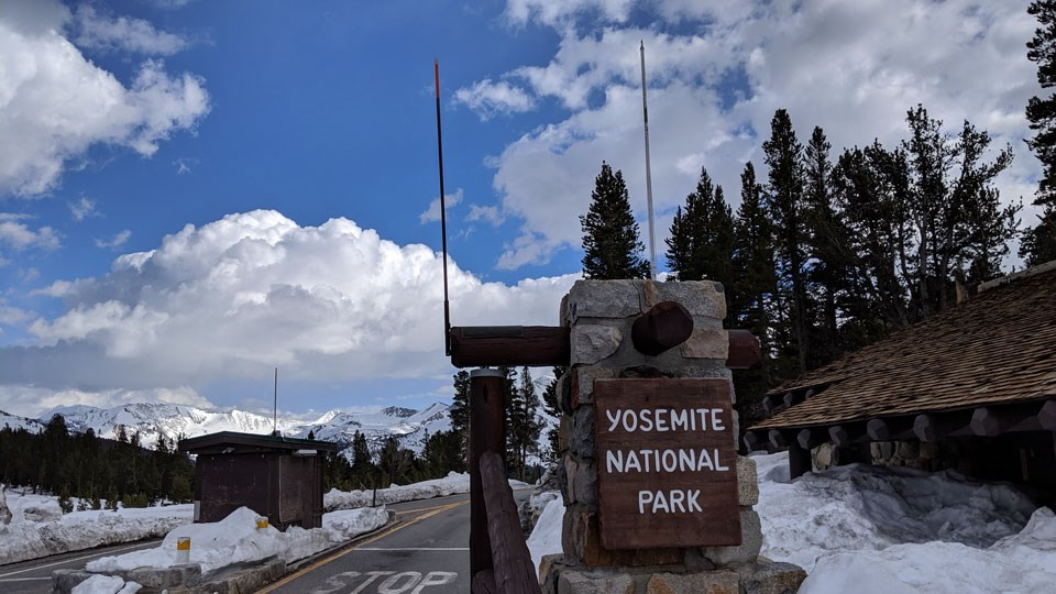 Yosemite National Park entrance sign at Tioga Pass with snowy mountains and plowed road in background