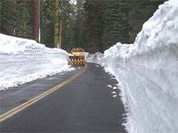 Plow clearing the Tioga Road; snowbanks on both sides of road