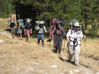 Several people hiking down a trail in single file
