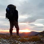 A hiker on a peak at sunset