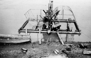 Historic photo of two people tending a fish wheel on the Yukon River.